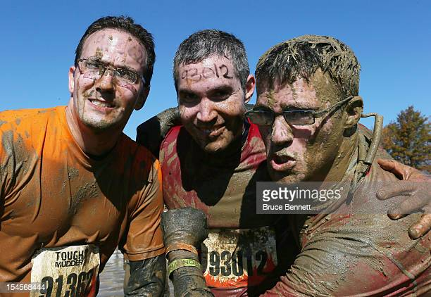 Participants pose for photos during the the Tough Mudder event at Raceway Park on October 21 2012 in Englishtown New Jersey