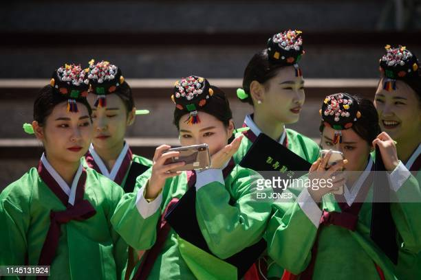 Participants pose for selfies as they attend a traditional Coming-of-Age Day ceremony to mark adulthood at Namsan hanok village in Seoul on May 20,...