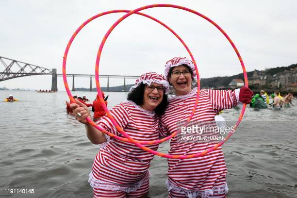 Participants pose in the water as they take part in the annual New Year's Day Loony Dook swim in the Firth of Forth in South Queensferry near...