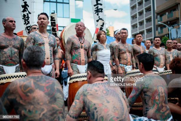 Participants pose to show their traditional Japanese tattoos related to the Yakuza during the annual Sanja Matsuri festival in the Asakusa district...