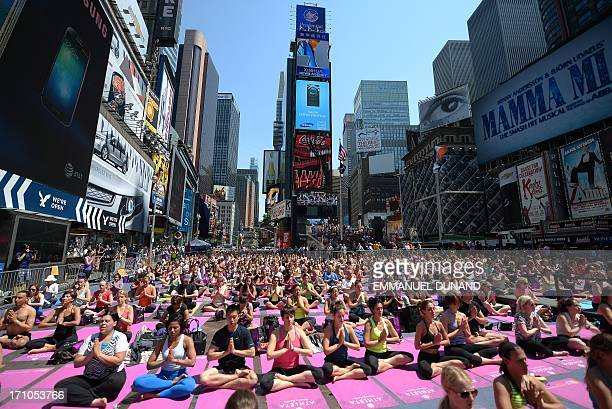 Participants practice yoga as part of a series of mass yoga classes set on Times Square to celebrate the summer solstice in New York June 21 2013 AFP...