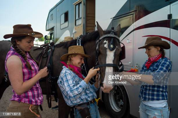 Participants prepare the tack on a horse ahead of the annual 'London Harness Horse Parade' on Easter Monday at The South of England Event Centre on...
