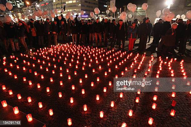 Participants prepare to release balloons while standing next to a sea of candles at the conclusion of a march to mourn the victims of AIDS on...
