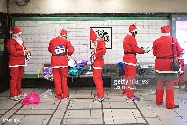 Participants put on their costumes at Clapham Common Underground Station as the prepare to take part in a charity 'Santa Dash' 5k and 10k runs around...