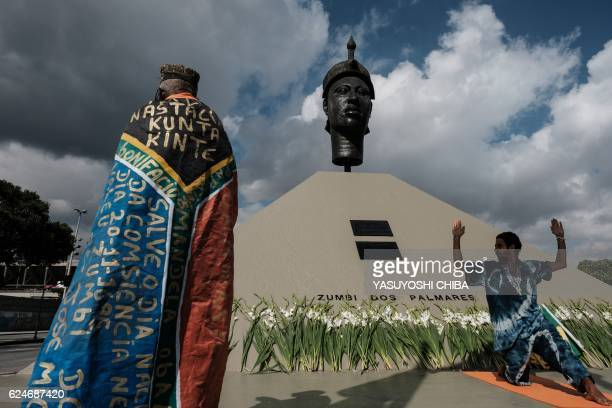 Participants react in front of the monument to Zumbi dos Palmares the AfroBrazilian resistance leader of the Quilombo dos Palmares slaves uprising...