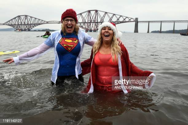 TOPSHOT Participants react in the water as they take part in the annual New Year's Day Loony Dook swim in the Firth of Forth in South Queensferry...