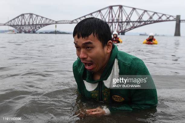 Participants react in the water as they take part in the annual New Year's Day Loony Dook swim in the Firth of Forth in South Queensferry near...