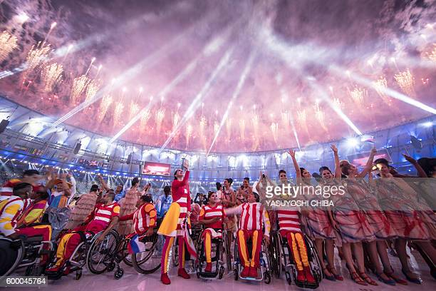 TOPSHOT Participants react under fireworks during the opening ceremony of the Rio 2016 Paralympic Games at the Maracana stadium in Rio de Janeiro on...