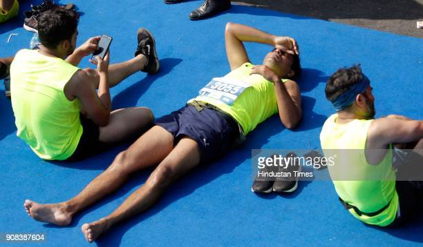 Participants relax near the finish line after Mumbai Marathon near CST station on January 21 2018 in Mumbai India