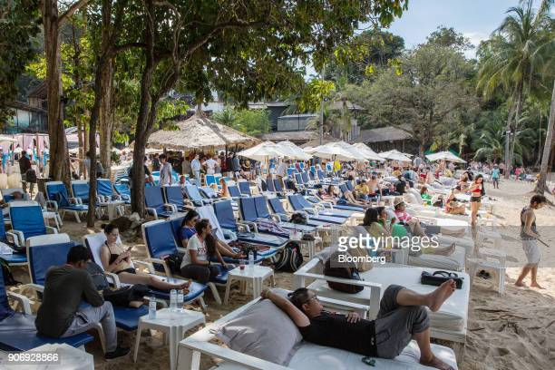 Participants relax on sun loungers during a Coinsbank Blockchain Cruise Asia conference event at Paradise Beach in Phuket Thailand on Wednesday Jan...