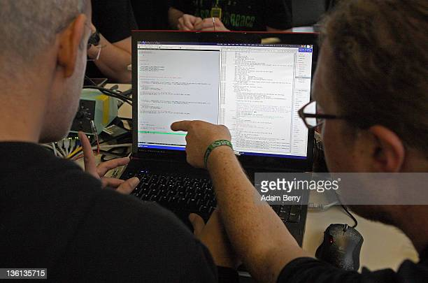 Participants review lines of code on a laptop on the first day of the 28th Chaos Communication Congress Behind Enemy Lines computer hacker conference...