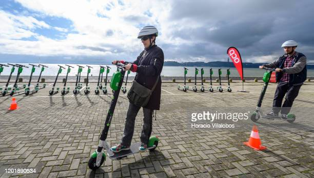 Participants ride by a row of parked LimeS escooters during a First Ride Academy workshop on good driving and parking practices organized by Lime the...