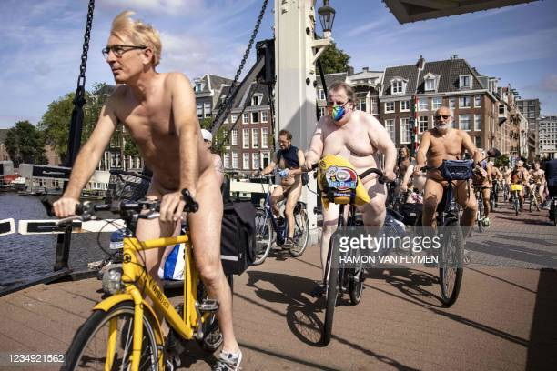 Participants ride their bicycles during the World Naked Bike Ride on August 28, 2021 in Amsterdam, The Netherlands. - The naked bike ride is...