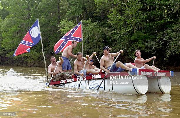 Participants row a homemade raft along the Oconee River during a raft race as part of the 6th annual Summer Redneck Games July 7 2001 in East Dublin...