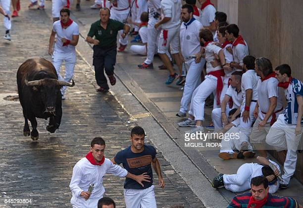 TOPSHOT Participants run ahead of Fuente Ymbro fighting bulls on the first day of the San Fermin bull run on July 7 in Pamplona northern Spain On...