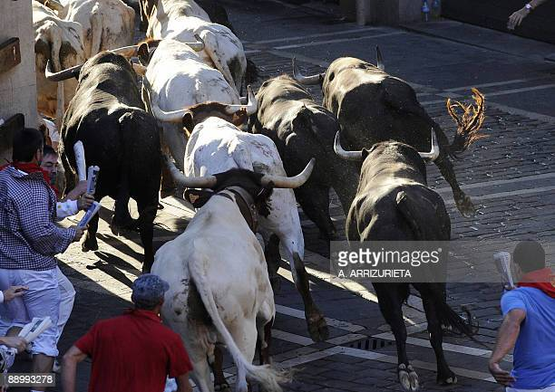 Participants run ahead of Fuente Ymbro fighting bulls on the seventh day of the San Fermin Festival bull run on July 13 in Pamplona northern Spain...