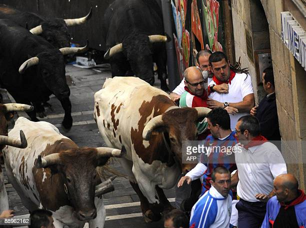 Participants run ahead of Jandilla fighting bulls on the fourth bull run of the San Fermin festival on July 10 in Pamplona northern Spain A man was...