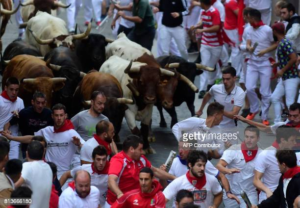 Participants run ahead of Nunez del Cuvillo's fighting bulls during the seventh bull run of the San Fermin festival in Pamplona northern Spain on...