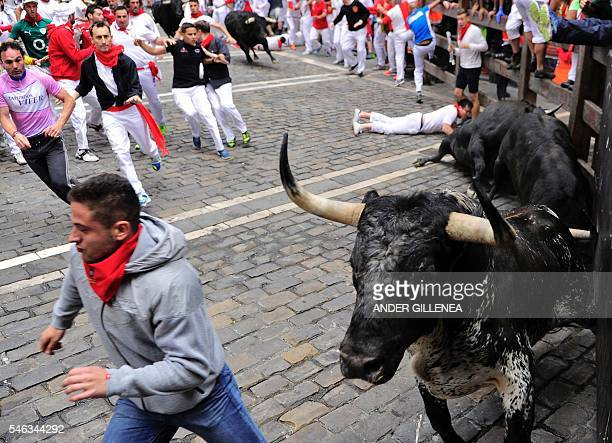 Participants run ahead of Victoriano del Rio Cortes' fighting bulls on the sixth day of the San Fermin bull run festival in Pamplona northern Spain...