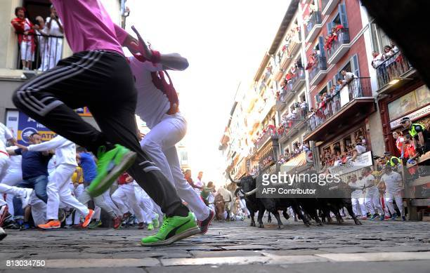 Participants run ahead of Victoriano del Rio's fighting bulls during the sixth bull run of the San Fermin festival in Pamplona northern Spain on July...