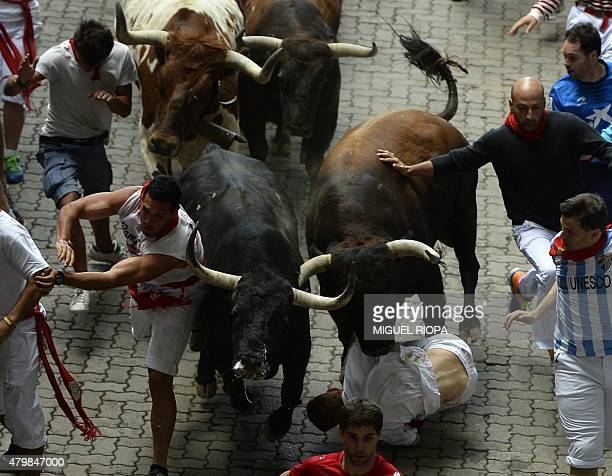 Participants run and fall in front of Del TajoLa Reina's bulls during the second 'encierro' of the San Fermin Festival in Pamplona northern Spain on...