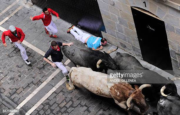 Participants run behind Miura's fighting bulls as another lies on the ground on the last day of the San Fermin bull run festival in Pamplona northern...