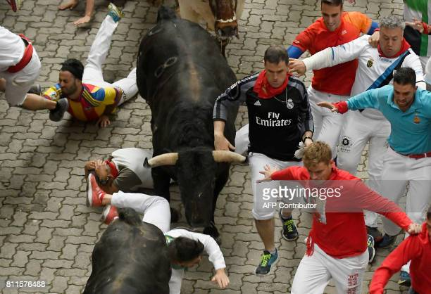 Participants run beside Fuente Ymbro's fighting bulls during the fourth bull run of the San Fermin festival in Pamplona northern Spain on July 10...