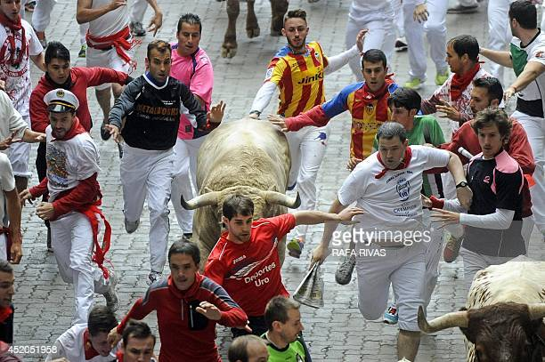 Participants run in front of a Fuente Ymbro bull during the sixth bull run of the San Fermin Festival in Pamplona northern Spain on July 12 2014 The...