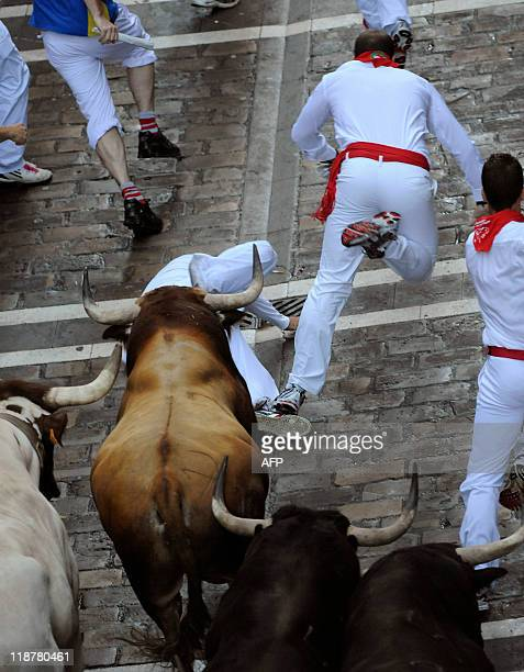 Participants run in front of Fuente Ymbro's fighting bulls during the fifth San Fermin Festival bull run on July 11 in Pamplona northern Spain The...