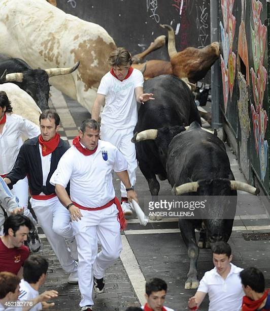 Participants run in front of Miura bulls during the last bull run of the San Fermin Festival in Pamplona northern Spain on July 14 2014 AFP PHOTO/...