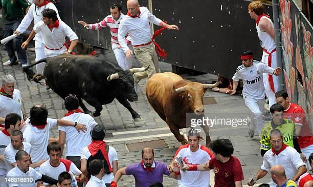 Participants run in front of TorrehandillaTorreherberos' bulls during the last San Fermin Festival bull run on July 14 in Pamplona northern Spain The...