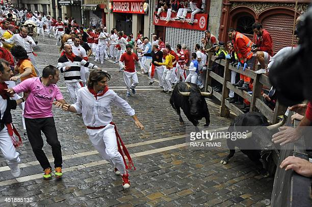 Participants run in front of Victoriano del Rio Cortes' bulls during the third bullrun of the San Fermin Festival in Pamplona northern Spain on July...
