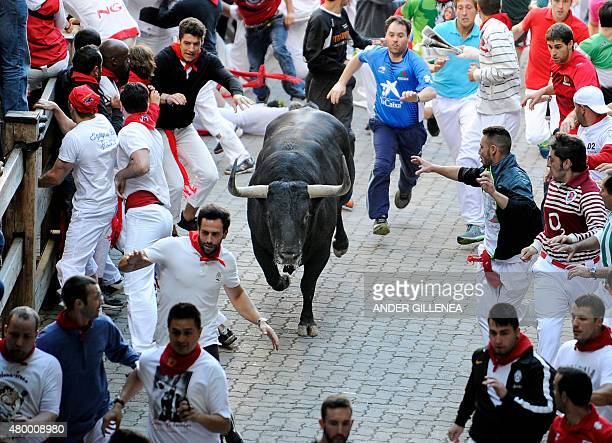 Participants run in front of Victoriano del Rio Cortes' bulls during the third 'encierro' of the San Fermin Festival in Pamplona northern Spain on...