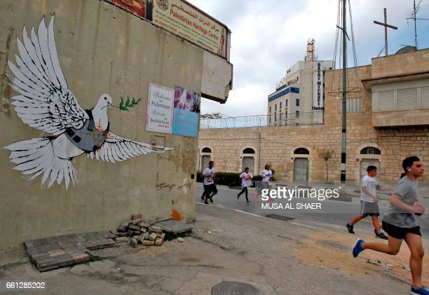 Participants run in the biblical West Bank town of Bethlehem during the 5th Palestine Marathon on March 31 2017 / AFP PHOTO / Musa AL SHAER
