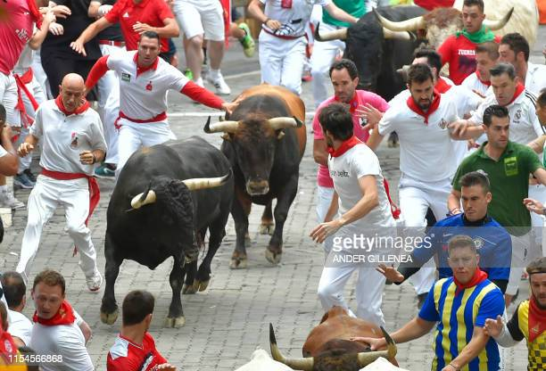 Participants run next to a Cebada Gago fighting bulls on the second bullrun of the San Fermin festival in Pamplona northern Spain on July 8 2019 On...