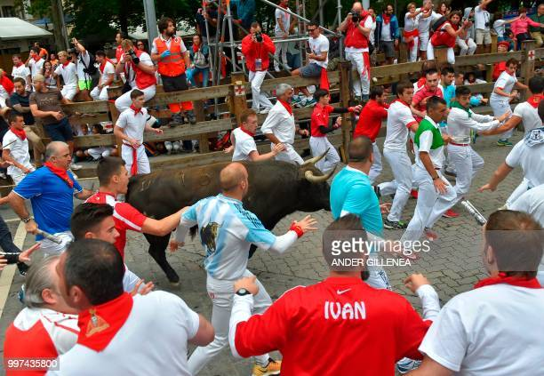 Participants run next to a Jandilla fighting bull during the seventh bullrun of the San Fermin festival in Pamplona northern Spain on July 13 2018...