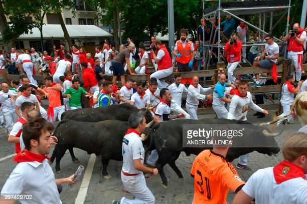 Participants run next to a Jandilla fighting bull on the seventh bullrun of the San Fermin festival in Pamplona northern Spain on July 13 2018 Each...