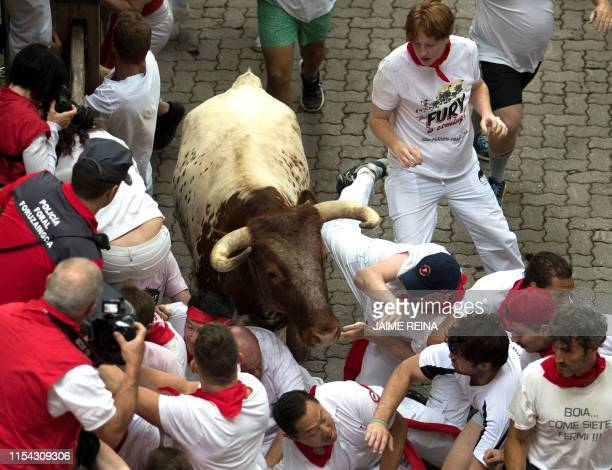 Participants run next to a Puerto de San Lorenzo fighting bull during the first bullrun of the San Fermin festival in Pamplona, northern Spain on...