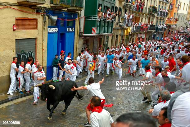 Participants run next to a Puerto de San Lorenzo's fighting bull on the first day of the San Fermin bull run festival in Pamplona northern Spain on...