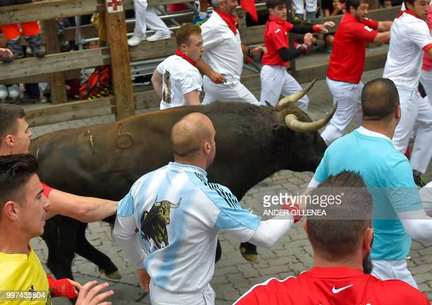 Participants run next to Jandilla fighting bull during the seventh bullrun of the San Fermin festival in Pamplona northern Spain on July 13 2018 Each...