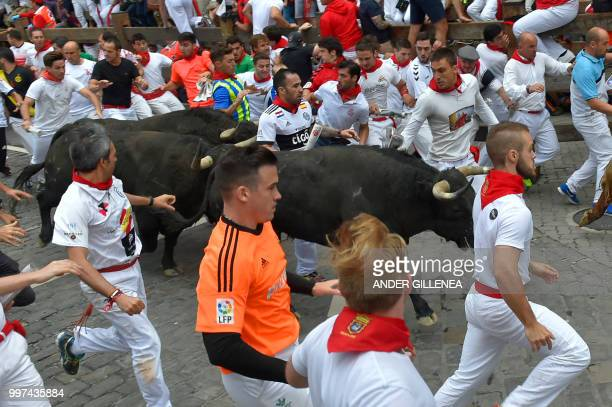 Participants run next to Jandilla fighting bulls during the seventh bullrun of the San Fermin festival in Pamplona northern Spain on July 13 2018...