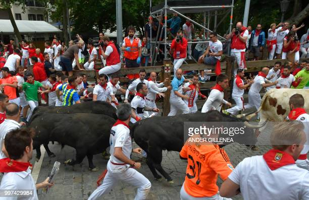 Participants run next to Jandilla fighting bulls on the seventh bullrun of the San Fermin festival in Pamplona northern Spain on July 13 2018 Each...