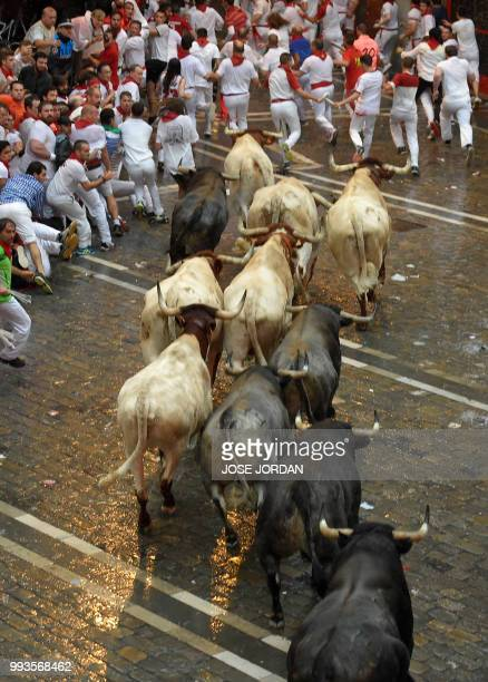 Participants run next to Jose Escolar fighting bulls on the second day of the San Fermin bull run festival in Pamplona northern Spain on July 8 2018...
