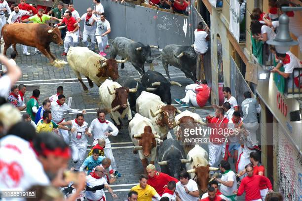 Participants run next to Miura fighting bulls on the last bullrun of the San Fermin festival in Pamplona northern Spain on July 12 2019 People from...