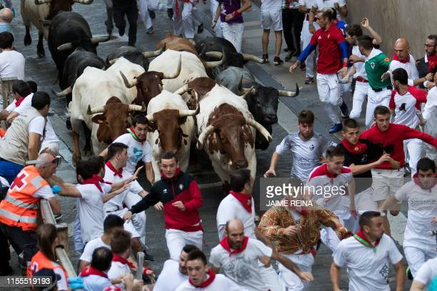 Participants run next to Miura fighting bulls on the last bullrun of the San Fermin festival in Pamplona, northern Spain, on July 12, 2019. - People...