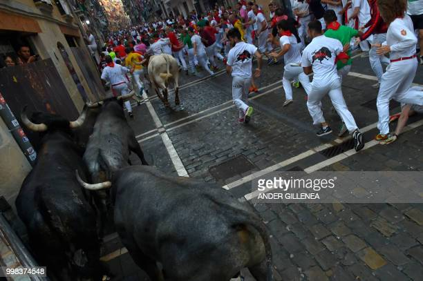 Participants run next to Miura fighting bulls on the last bullrun of the San Fermin festival in Pamplona northern Spain on July 14 2018 Each day at...