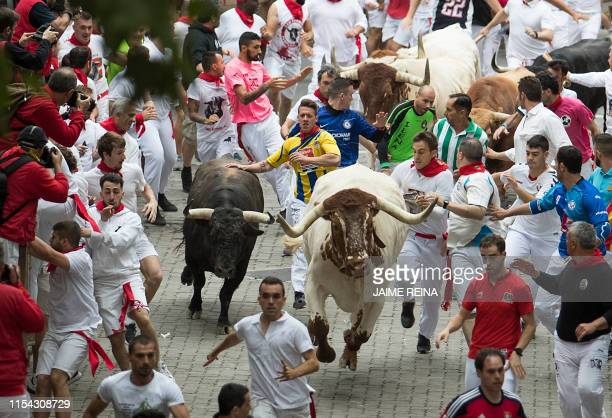 Participants run next to Puerto de San Lorenzo fighting bulls during the first bullrun of the San Fermin festival in Pamplona northern Spain on July...