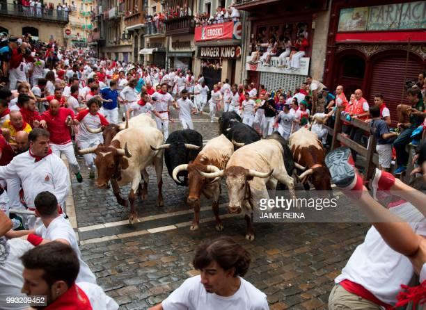 Participants run next to San Lorenzo 's fighting bulls on the first day of the San Fermin bull run festival in Pamplona northern Spain on July 7 2018...