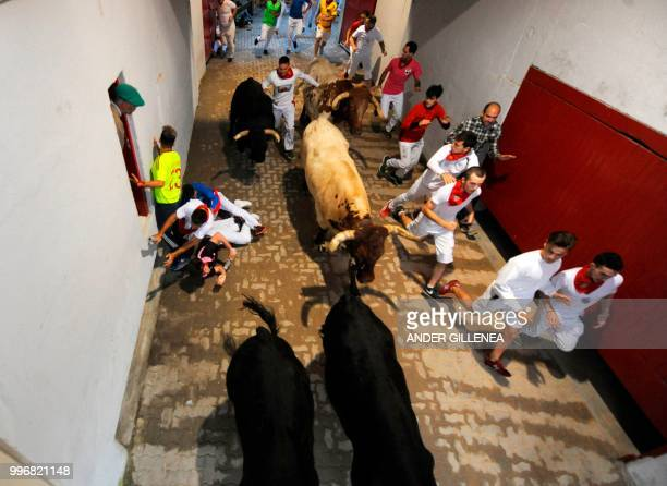 Participants run next to Victoriano del Rio fighting bulls on the sixth bullrun of the San Fermin festival in Pamplona northern Spain on July 12 2018...