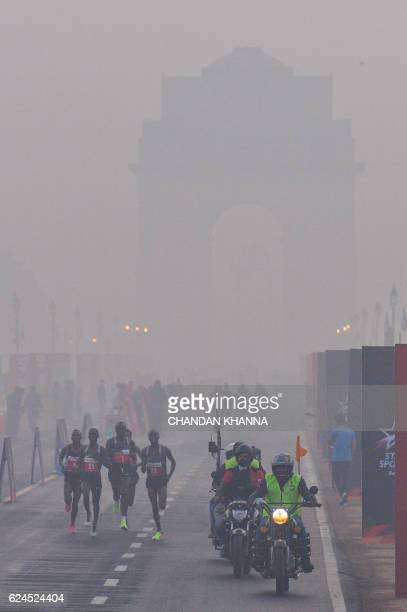Participants run on Rajpath in front of India Gate obscured by fog and smog at the Delhi Half Marathon in New Delhi on November 20 2016 / AFP PHOTO /...
